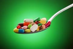 Diverses pilules, capsules et comprimés empilés sur une cuillère Photo stock