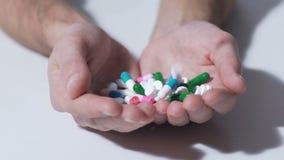 Diverses pilules tombant dans des mains de personne, industrie pharmaceutique, médicament banque de vidéos