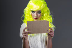 Diversión, adolescente con la peluca amarilla fluorescente, llevando una cartulina Imágenes de archivo libres de regalías