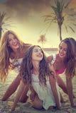 Diversión adolescente de las muchachas de los mejores amigos en una puesta del sol de la playa Fotos de archivo libres de regalías