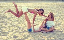 Diversión adolescente de las muchachas de los mejores amigos en una puesta del sol de la playa Foto de archivo libre de regalías
