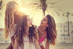 Diversión adolescente de las muchachas de los mejores amigos en una puesta del sol de la playa Fotos de archivo
