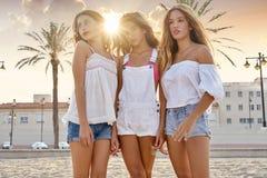 Diversión adolescente de las muchachas de los mejores amigos en una puesta del sol de la playa Foto de archivo