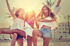 Diversión adolescente de las muchachas de los mejores amigos en una puesta del sol de la playa Fotografía de archivo libre de regalías
