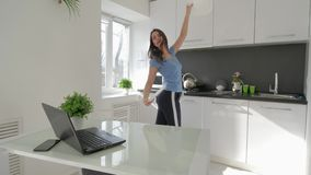 Diversión casera, baile alegre de la muchacha del ama de casa con las placas en manos en la cocina metrajes