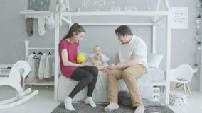 Diversión de baile del bebé lindo que se sienta en cama con los padres almacen de metraje de vídeo