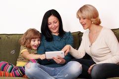 Diversión de la familia con PC de la tablilla Foto de archivo