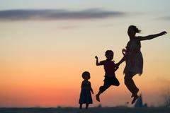 Diversión de la familia en la playa de la puesta del sol Fotografía de archivo