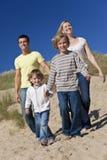 Diversión de la madre, del padre y de la familia de dos muchachos en la playa Foto de archivo