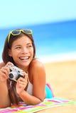 Diversión de la mujer de la playa del verano que sostiene la cámara Fotografía de archivo libre de regalías