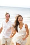Diversión de la playa - junte la risa y el funcionamiento junto Imágenes de archivo libres de regalías