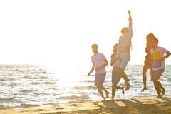 Diversión de los amigos en la playa bajo luz del sol de la puesta del sol fotografía de archivo