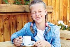 Diversión de risa de la muchacha mientras que se sienta en un café en un café de la calle Fotos de archivo