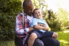 Diversión de And Son Having del padre en el oscilación del neumático en jardín Fotografía de archivo libre de regalías