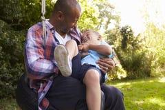 Diversión de And Son Having del padre en el oscilación del neumático en jardín Fotos de archivo libres de regalías