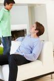 Diversión de And Son Having del padre en Sofa Together fotografía de archivo libre de regalías
