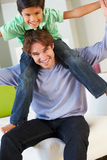 Diversión de And Son Having del padre en Sofa Together imagen de archivo