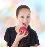 Diversión del adolescente que come una manzana roja Imagen de archivo libre de regalías