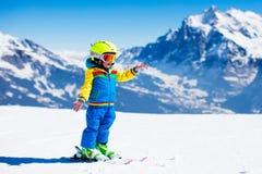Diversión del esquí y de la nieve para el niño en montañas del invierno imagen de archivo libre de regalías