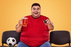 Diversión del fútbol y del deporte - feliz y hombre gordo que ve la TV, tomando la cerveza y el balón de fútbol en fondo amarillo Fotografía de archivo