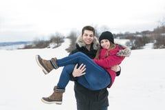 Diversión del havinf de dos adolescentes en el campo de nieve Foto de archivo libre de regalías