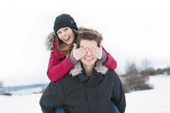 Diversión del havinf de dos adolescentes en el campo de nieve Imagen de archivo libre de regalías