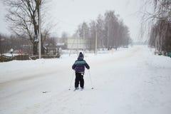 Diversión del invierno el niño está esquiando alrededor del pueblo fotos de archivo