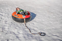 Diversión del invierno en un tubo inflable Imagen de archivo libre de regalías