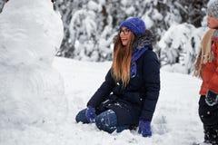 Diversión del invierno la muchacha en un sombrero hecho punto esculpe un muñeco de nieve foto de archivo