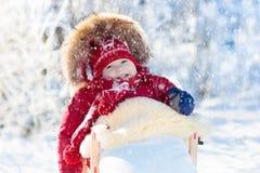 Diversión del trineo y de la nieve para los niños Bebé sledding en parque del invierno Fotos de archivo libres de regalías