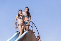 Diversión del verano de la diapositiva de la piscina del muchacho de las muchachas Imagen de archivo libre de regalías