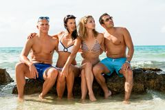 Diversión feliz joven del havin de los amigos en la playa foto de archivo libre de regalías