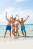Diversión feliz joven del havin de los amigos en la playa foto de archivo