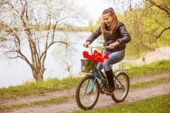 Diversión joven y mujer feliz una bicicleta de los niños que montan Imagen de archivo