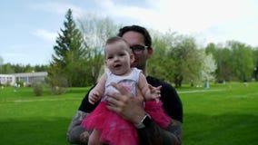 Diversión La hija en las manos del papa alcanza para la cámara almacen de video