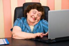 Diversión mayor del havinf de la mujer de la oficina en la computadora portátil Imágenes de archivo libres de regalías