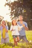 Diversión para el niño femenino con las burbujas de jabón Imagen de archivo