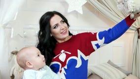 Diversión que juega durante las vacaciones de invierno, bebé en los brazos de su madre, familia feliz de la familia que sonríe di almacen de metraje de vídeo