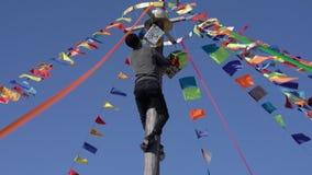 Diversión rusa de la tradición: hombre que sube al top del polo de madera para los premios y los regalos