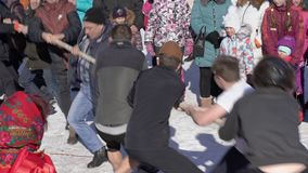 Diversión rusa - dos grupos de oposición de hombres tiran de la cuerda en diversas direcciones