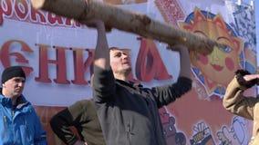 Diversión rusa - el hombre aumenta el registro del abedul sobre su cabeza durante las festividades Maslenitsa