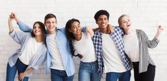 Diversi adolescenti che abbracciano e che si divertono sopra la parete bianca fotografia stock