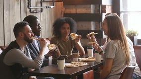 Diversi amici che mangiano insieme pizza, pranzando nel ristorante della pizzeria archivi video