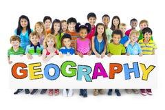 Diversi bambini allegri che tengono la geografia di parola Immagini Stock Libere da Diritti