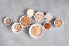 Diversi cereali e fagioli in piatti bianchi sulla tavola strutturata grigia immagine stock