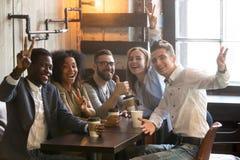 Diversi colleghi millenari sorridenti che posano per l'immagine in caffè Fotografie Stock Libere da Diritti