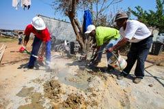 Diversi membri della comunità che costruiscono una casa di basso costo a Soweto Fotografia Stock