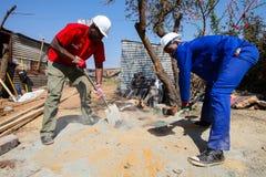 Diversi membri della comunità che costruiscono una casa di basso costo a Soweto Immagini Stock