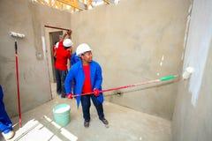 Diversi membri della comunità che dipingono una casa di basso costo a Soweto Fotografie Stock