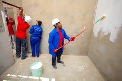 Diversi membri della comunità che dipingono una casa di basso costo a Soweto Fotografie Stock Libere da Diritti